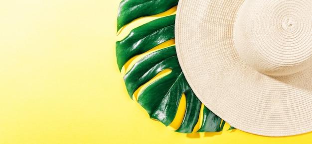 明るい黄色の日当たりの良い背景に麦わら帽子 無料写真