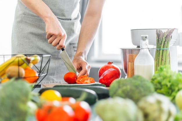 Молодой человек шеф-повар готовит полезный салат Бесплатные Фотографии
