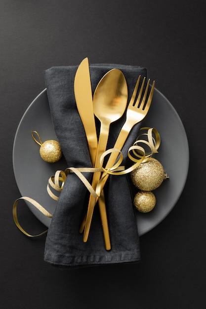 Золотые столовые приборы подаются на тарелку на рождественский ужин Premium Фотографии