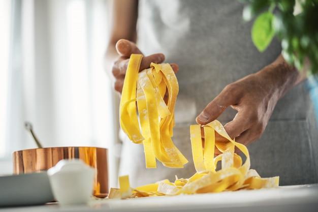 Паста шеф-повар делает свежие итальянские макароны Premium Фотографии