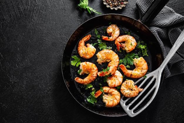 Жареные креветки на сковороде на темном Premium Фотографии