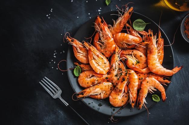 Жареные креветки со специями на тарелке Premium Фотографии