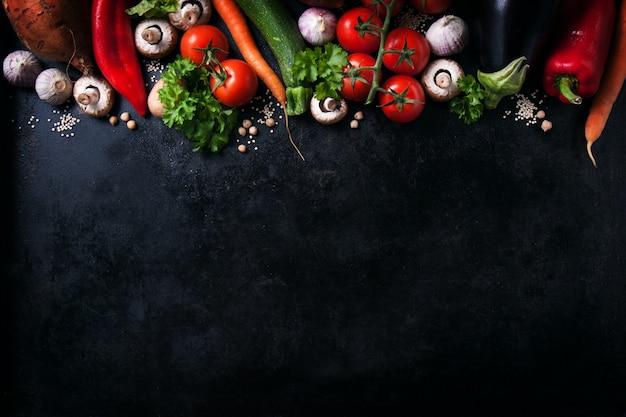 メッセージのためのスペースを持つ黒のテーブルの上に様々な野菜 無料写真