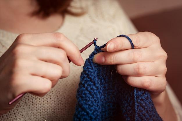 かぎ針編み。女性かぎ針編みダークブルーの糸。手のクローズアップ。 Premium写真