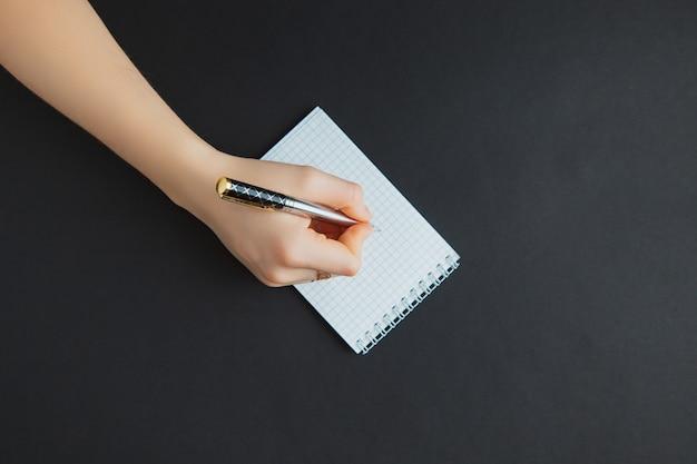 黒いテーブルでメモ帳で書く婦人 Premium写真