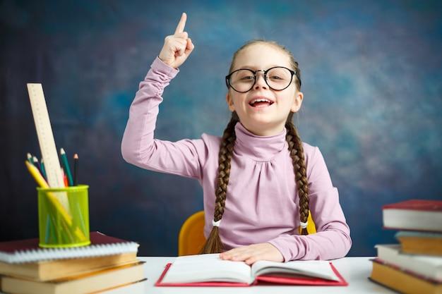 Умная начальная школьница делает домашнее задание Premium Фотографии