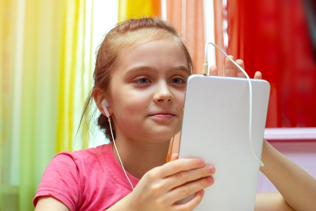 Маленькая девочка с планшетом. общение, обучение, игры ребенка, подростка с современным устройством. интерактивные социальные технологии в мире Premium Фотографии