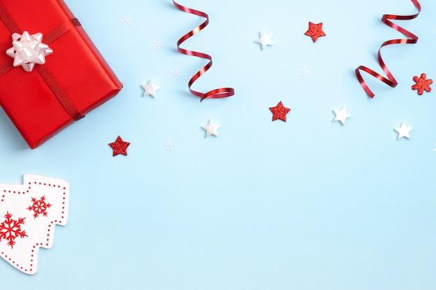 赤と白のクリスマスのおもちゃ、青い表面のギフトボックス。 Premium写真