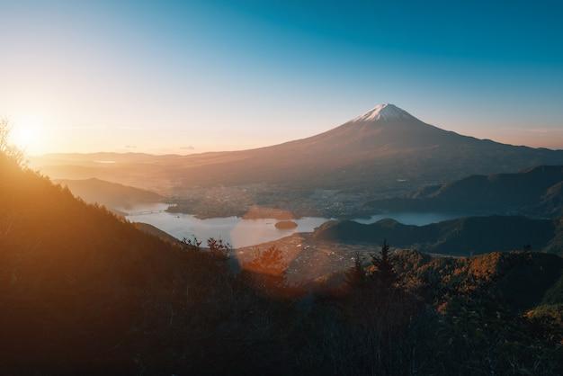 富士河口湖の日の出の秋の紅葉と河口湖の上の富士山の風景画像。 Premium写真