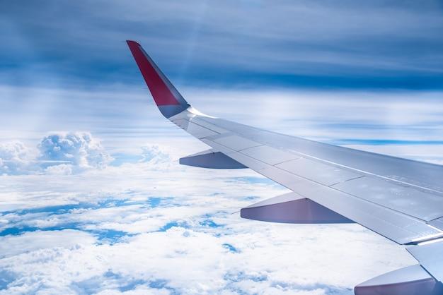窓から雲と青い空に飛行機の翼。 Premium写真