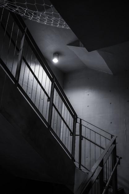 Одиночная лампочка, освещающая темную внутреннюю лестницу Бесплатные Фотографии