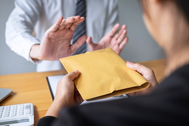 贈収賄および汚職防止の概念、ビジネスマンを拒否し、投資取引の契約契約を受け入れるために、ビジネスの人々から封筒の申し出でお金の紙幣を受け取らない Premium写真