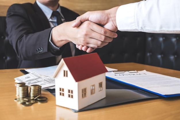 不動産、ブローカー、およびクライアントが住宅ローンの住宅ローンの申し込みに関する契約承認済みの申請書に署名した後、握手する成功した取引の画像 Premium写真