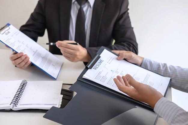 Работодатель или вербовщик держит чтение резюме во время разговора о своем профиле кандидата, работодатель в костюме проводит собеседование, менеджер по трудоустройству и концепции найма Premium Фотографии