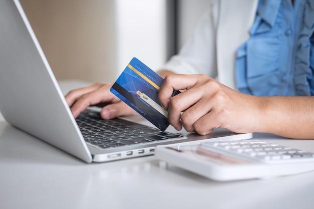 クレジットカードを保持し、オンラインショッピングや支払いのためにラップトップに入力する手が購入を行う Premium写真