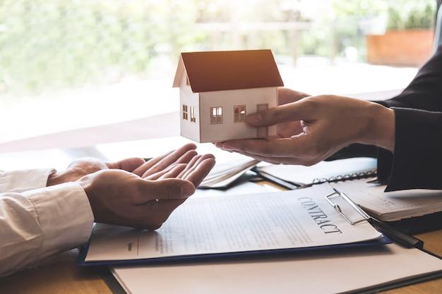 Агент по недвижимости отправляет клиенту модель дома после подписания договора подряда недвижимости с утвержденной формой заявки на ипотеку, касающейся предложения ипотечного кредита и страхования дома Premium Фотографии