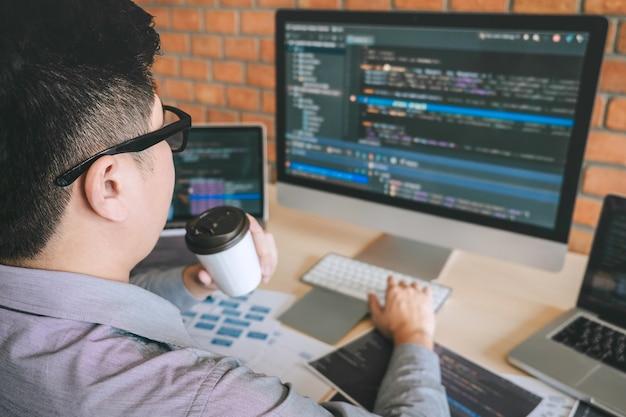 ソフトウェアのウェブサイトの設計とコーディング技術に取り組むプロの開発者プログラマー、会社のオフィスでコードとデータベースを書く、グローバルなサイバー接続技術 Premium写真