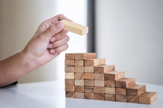 木製ブロックを積み上げて土台を作る人の手の配置の画像 Premium写真
