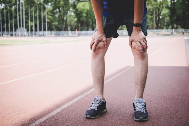 若いフィットネス選手の男は、中に休憩し、道路のトラックで疲れて、運動トレーニングウェルネス Premium写真