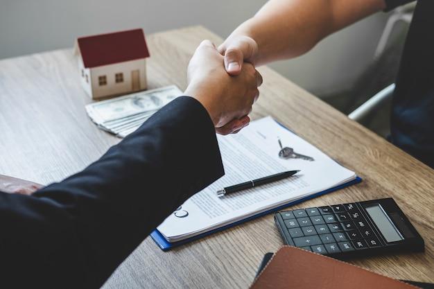 Завершая успешную сделку с недвижимостью, брокер и клиент пожимают друг другу руки после подписания одобренной заявки, касающейся предложения по ипотечному кредиту и страхованию дома. Premium Фотографии