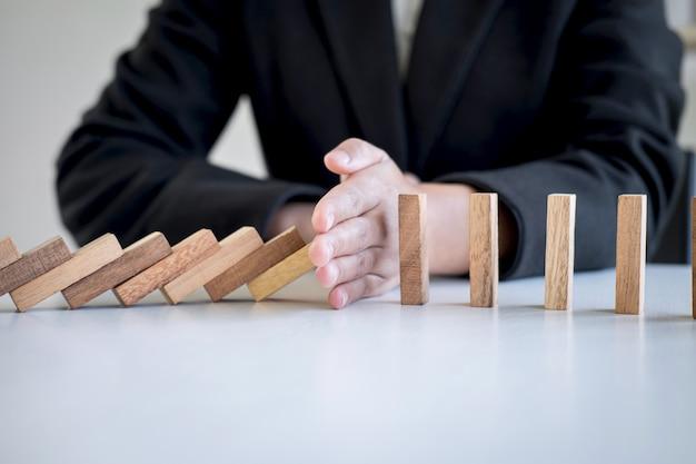連続倒れたブロックからの手停止落下崩壊木製ブロックドミノ効果 Premium写真
