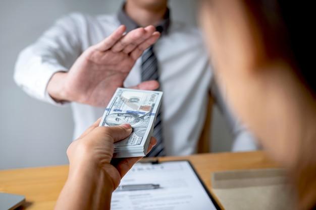 ビジネスの男性を拒否し、女性から封筒の提供でお金の紙幣を受け取らない Premium写真