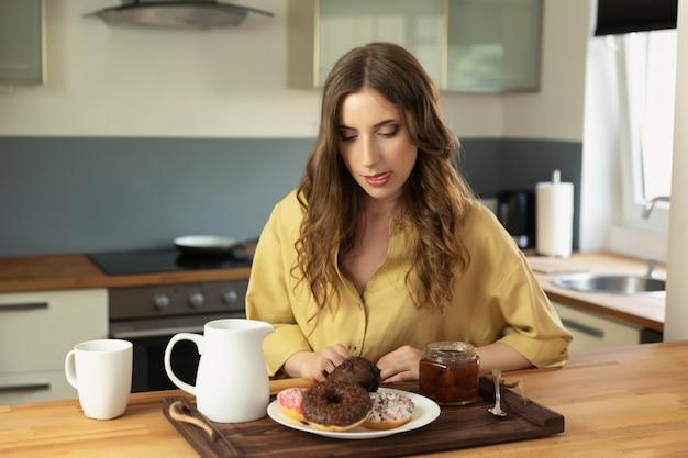Молодая красивая девушка, имея завтрак у себя дома на кухне. Premium Фотографии