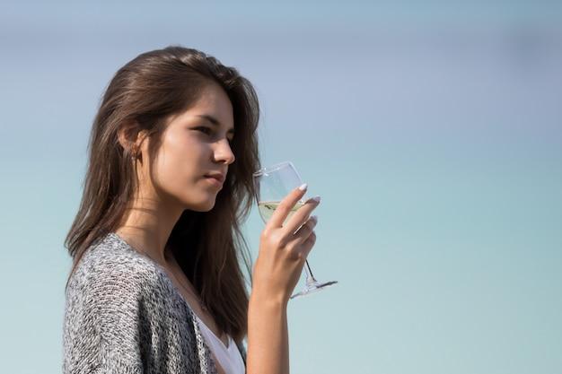 Молодая красивая девушка пьет вино из стекла. Premium Фотографии