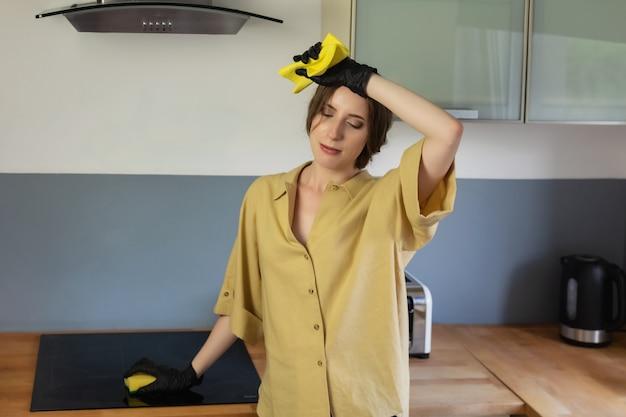若い女性が台所で掃除し、皿洗いをします。彼女は疲れていて、それをする必要があるという事実に満足していません。 Premium写真