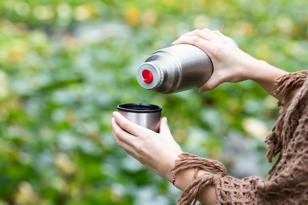 魔法瓶からマグカップで温かい飲み物を注いで、ハイキング中にお茶を飲む女性。 Premium写真
