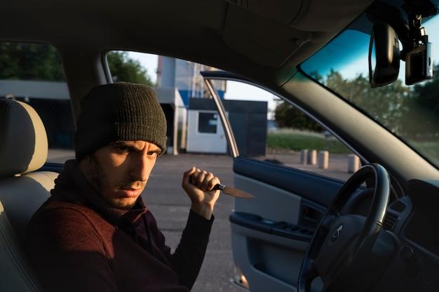 ナイフで武装した男が駐車場で無防備な女性を襲った。強姦犯は被害者を誘拐しようとしています。 Premium写真