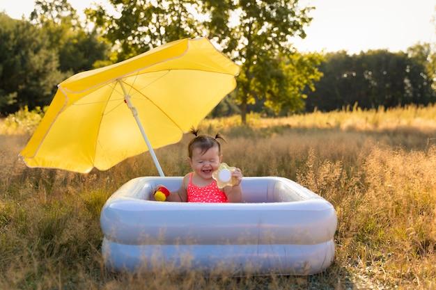 少女は、膨脹可能なプールを浴びます。 Premium写真