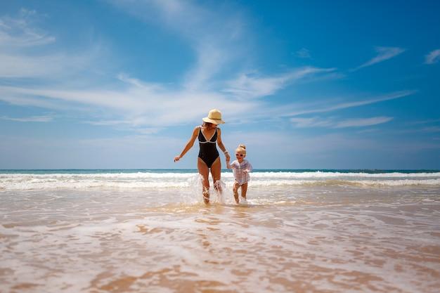 Счастливая и активная мама и дочка бегают по воде и играют на пляже. Premium Фотографии