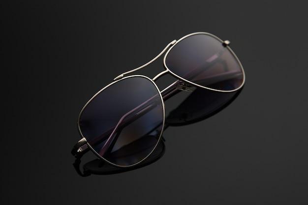 サングラスメガネは、ドロップ、警察、パイロット、スパイ、偏光フィルター付きのスタイリッシュなグラデーション背景の金属フレームを形成します。 Premium写真