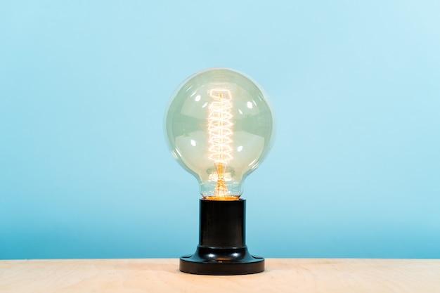 エジソンの電気ランプ、青色の背景に。独創的なアイデア。ロフトスタイル、広告スペース。安全な照明、デザイン。 Premium写真