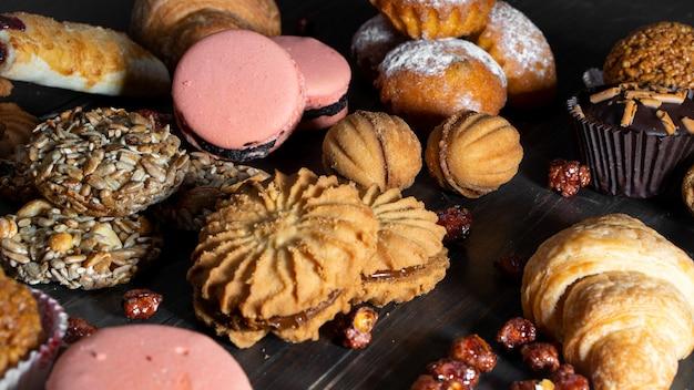 クッキー、マフィン、クロワッサン、木製のテーブルにパスタベーキングお菓子芽スタイル。コーヒーまたは紅茶の美味しいセット。 Premium写真