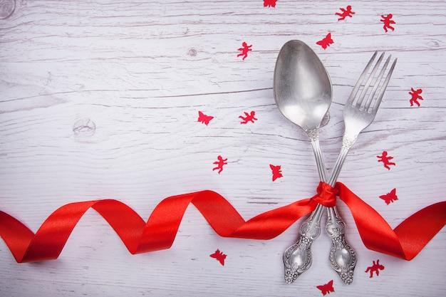 ビンテージスプーンとフォーク赤い木製のテーブルの上のバレンタインデーのための赤いテープ、天使と蝶。 Premium写真