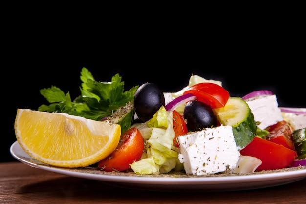 フェタチーズ、オリーブ、レタス、トマト、キュウリ、黒の背景にレモンのサラダ。 Premium写真