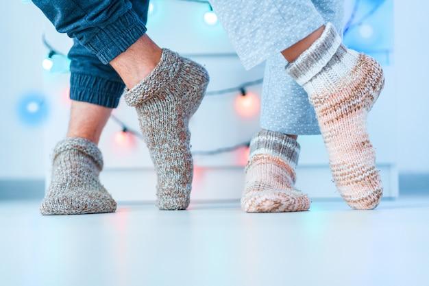 Романтическая влюбленная семейная пара в теплых вязаных мягких уютных носочках зимой в домашних условиях Premium Фотографии