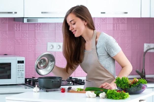 自宅で新鮮な熟した野菜から夕食を調理するエプロンの女性。清潔な食べ物と健康的なライフスタイル Premium写真