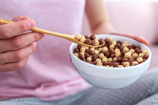 スプーンとボウルのシリアル朝食用チョコレートボールの完全なクローズアップ Premium写真