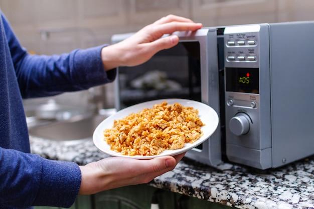 自宅で昼食のために自家製のピラフのプレートを温めるために電子レンジを使用します。あったかい食事 Premium写真
