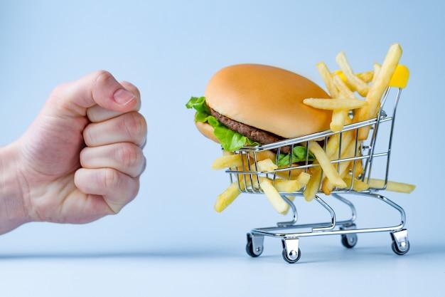 食べ物と食事のコンセプト。フライドポテトとスナックのハンバーガー。太りすぎと肥満との戦い。ジャンク品、不健康な食べ物の拒否 Premium写真