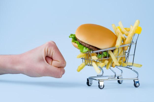 フライドポテトとスナックのハンバーガー。ファーストフード中毒。太りすぎと肥満との戦い。ジャンク品、不健康な食べ物の拒否 Premium写真