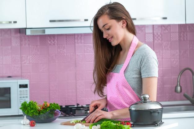 健康的な新鮮なサラダや自宅の台所で料理の完熟野菜を刻んで調理女性 Premium写真