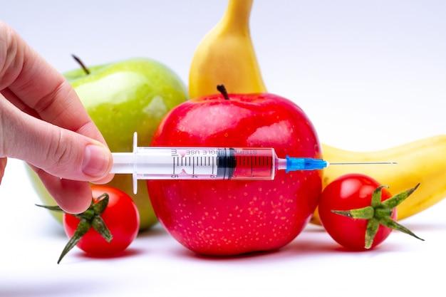 Пестициды и нитраты вводятся в овощи и фрукты с помощью шприца. концепция гмо и генетически модифицированный организм. гмо бесплатно и натуральные полезные продукты без химических добавок. Premium Фотографии