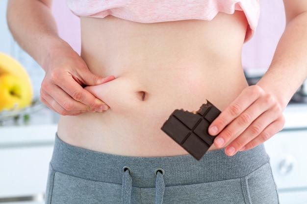 腰に余分な脂肪をつまんで、不健康なジャンク炭水化物の甘い食べ物のために余分な体重を増やしている女性 Premium写真