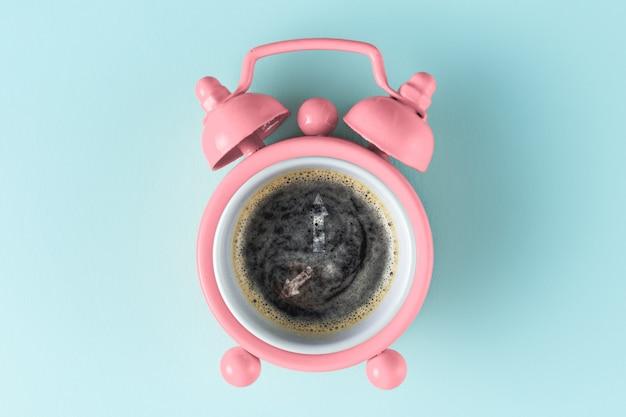 ピンクの目覚まし時計とコーヒー Premium写真