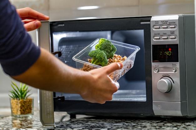 女性の手は、ブロッコリーとそばのプラスチック容器を電子レンジに入れます Premium写真