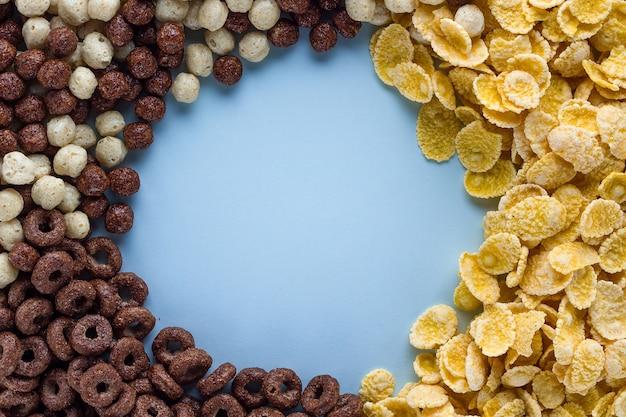 Смесь сухих, шоколадных шариков, колец и желтых кукурузных хлопьев для здоровых зерновых завтрака фоне рамки Premium Фотографии